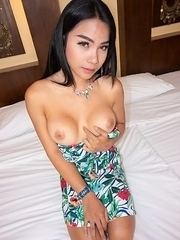 Shapely ladyboy Tata is smoking a cigarette out on the balcony. She comes inside the room and changes into a colorful strapless sundress.