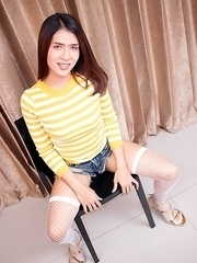 Ladyboy Bipor is wearing a striped yellow sweater with jean booty shorts and high heels.
